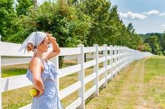 站立在乡下的近的篱芭和享受自然的俏丽的妇女 库存图片