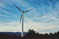 站立在乡下的风车反对与拷贝空间,位于领域的风轮机的多云天空背景, 库存照片