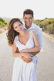 站立在乡下路的爱恋的夫妇 免版税库存图片