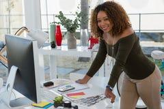 站立在书桌的微笑的女实业家在办公室 免版税库存图片