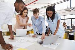 站立在书桌的年轻企业队工作在一个繁忙的办公室 免版税库存图片