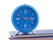 站立在书的闹钟 免版税库存照片