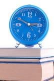 站立在书的闹钟 免版税库存图片