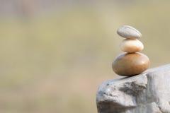 站立在互相的三块石头象征平衡 免版税库存图片