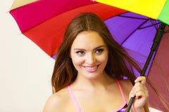 站立在五颜六色的彩虹伞下的妇女 免版税库存照片