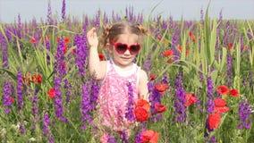 站立在五颜六色的草甸的小女孩 股票视频