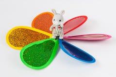 站立在五颜六色的轮转焰火中间的玩具兔宝宝 免版税库存照片