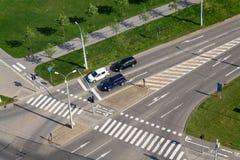 站立在交叉路的,鸟瞰图行人穿越道前面的汽车 免版税库存图片