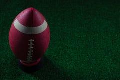 站立在人为草皮的持有人的橄榄球特写镜头 免版税库存图片