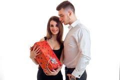 站立在人旁边和拿着一个大红色礼物特写镜头的迷人,微笑女孩 免版税库存图片