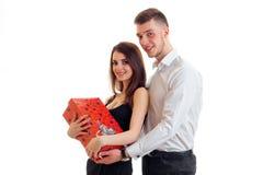 站立在人旁边和拿着一件大红色礼物的年轻美丽的女孩 免版税库存照片