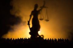 站立在人群后的被弄脏的大夫人正义雕象和标度剪影与剑的在晚上有有雾的火背景 在 免版税库存照片