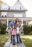 站立在他们的家前面的微笑的家庭画象 免版税库存照片