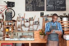 站立在他的咖啡馆的年轻企业家使用一种数字式片剂 免版税库存图片