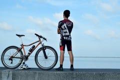 站立在他的在海洋断裂水的山自行车旁边的年轻男性骑自行车的人 免版税库存照片