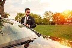 站立在他的汽车旁边的英俊的商人 免版税库存照片