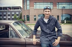 站立在他的汽车的愉快的年轻所有者画象  免版税库存图片