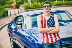 站立在他的汽车的成功的十几岁的男孩 免版税库存照片