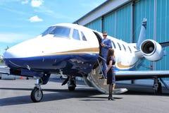 站立在企业喷气机的门的乘客 免版税图库摄影