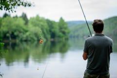 站立在伏尔塔瓦河银行的渔夫,钓鱼概念 免版税库存照片