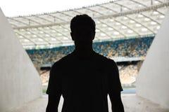 站立在体育场的一个人的剪影 免版税库存照片