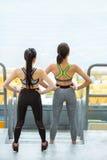 站立在体育场的两个年轻女运动员准备好训练 库存照片