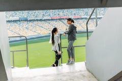 站立在体育场的扶手栏杆的两个年轻女运动员 免版税库存照片