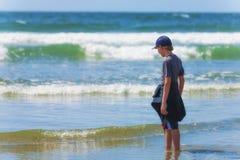 站立在俄勒冈海岸的海浪的男孩 库存照片