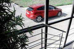 站立在修造附近的红色汽车 免版税库存图片