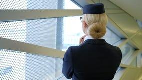 站立在候诊室佩带的帽子制服的白肤金发的空中小姐 影视素材