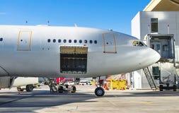 站立在停车场的航空器在机场,准备装载乘客行李 库存照片