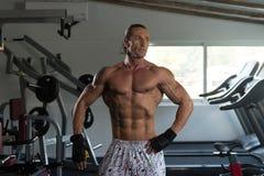 站立在健身房的严肃的爱好健美者 免版税库存照片
