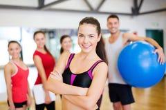 站立在健身房的小组前面的妇女 库存图片