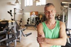 站立在健身房的成熟人画象 免版税库存照片