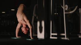 站立在健身房的手上的肌肉人在墙壁旁边进行俯卧撑 影视素材