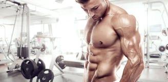 站立在健身房的肌肉爱好健美者人 免版税库存图片