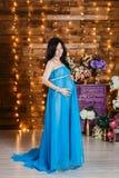 站立在充分的高度和神色的一件长的丝绸蓝色礼服的美丽的怀孕的深色的妇女在腹部 免版税库存照片