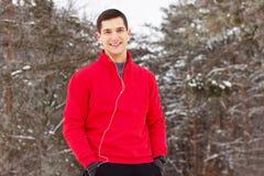 站立在公园和听的音乐的红色毛线衣的英俊的微笑的运动员 室外的活动 免版税库存照片