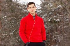 站立在公园和听的音乐的红色毛线衣的年轻和英俊的运动员 室外的活动 图库摄影