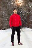 站立在公园和听的音乐的红色毛线衣的年轻和英俊的运动员 室外的活动 库存照片