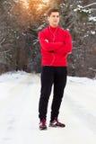 站立在公园和听的音乐的红色毛线衣的年轻和英俊的运动员 室外的活动 免版税图库摄影