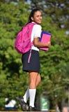 站立在公园的西班牙学校女孩 免版税库存图片
