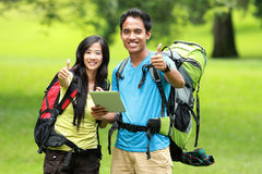 站立在公园的年轻亚洲夫妇拿着片剂个人计算机显示 库存照片