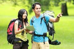 站立在公园的年轻亚洲夫妇拿着片剂个人计算机,人 免版税库存图片