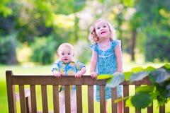 站立在公园长椅的兄弟和姐妹 库存照片