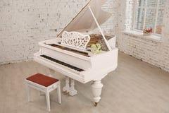 站立在典雅的白色内部的白色大平台钢琴 库存照片