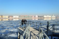 站立在内娃河的观察台的年轻夫妇在大学堤防对面在圣彼德堡 免版税库存图片