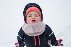站立在冬天公园的小女孩孩子 看照相机blowin 免版税库存图片