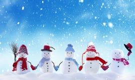 站立在冬天圣诞节风景的许多雪人 免版税库存照片