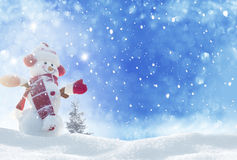 站立在冬天风景的雪人 免版税库存图片